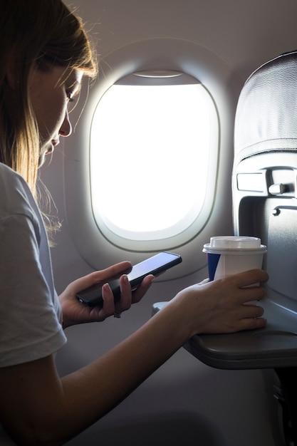 Mädchen, das einen kaffee hält und telefon betrachtet Kostenlose Fotos