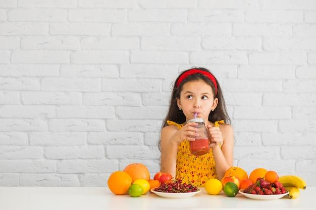 Mädchen, das erdbeeresmoothies mit bunten früchten auf dem schreibtisch trinkt Kostenlose Fotos
