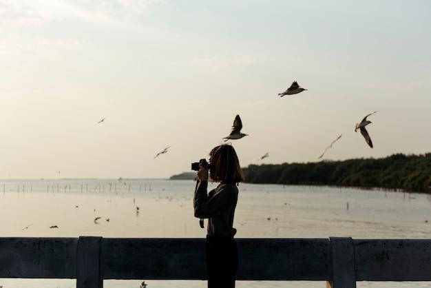 Mädchen, das fotos von den vögeln fliegen über den ozean macht Premium Fotos