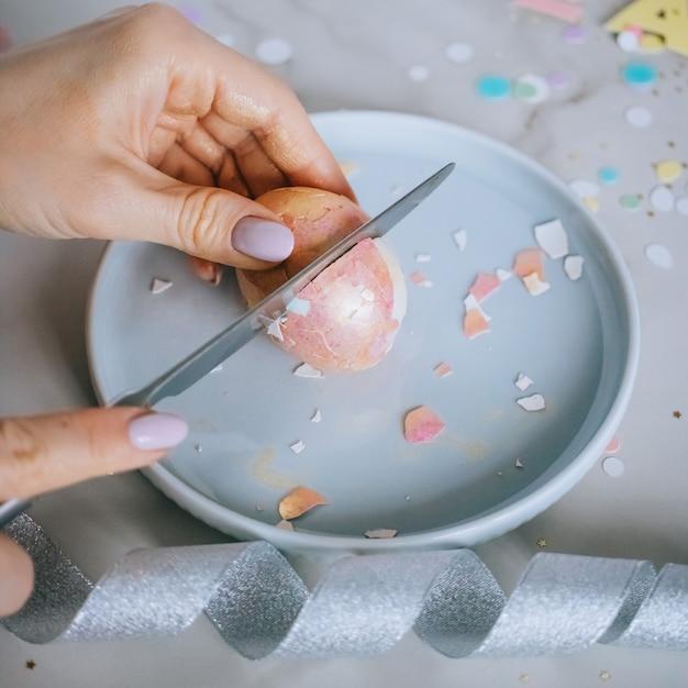 Mädchen, das goldene ostereier auf marmorhintergrund, konfetti, scheine, bänder schneidet. Premium Fotos
