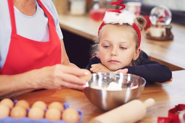 Mädchen, das großmutter beobachtet, die einen kuchen macht Kostenlose Fotos