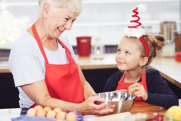 Mädchen, das großmutter hilft, kekse für weihnachten zu machen Kostenlose Fotos