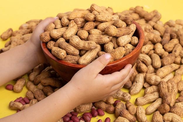 Mädchen, das hölzerne schüssel mit ungeschälten erdnüssen hält Premium Fotos