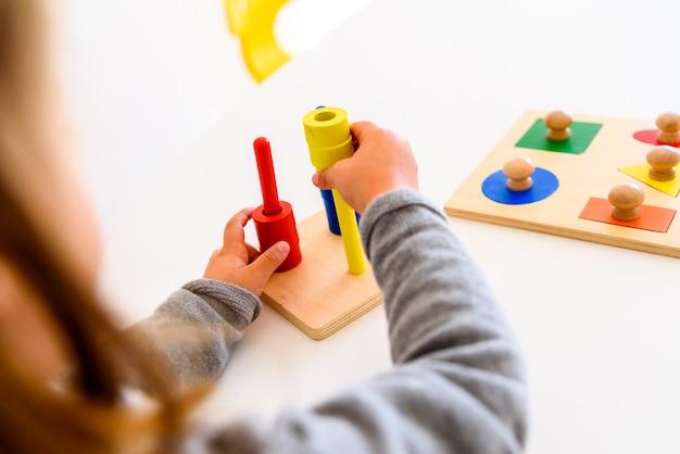 Mädchen, das ihre manuelle fingerfertigkeit mit einem sensorischen material von farben entwickelt. Premium Fotos