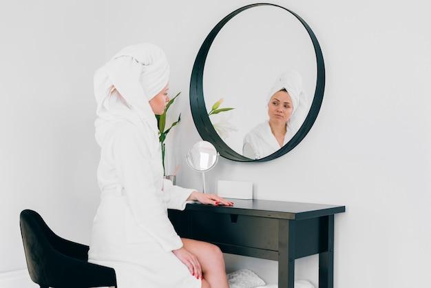 Mädchen, das ihre reflexion betrachtet Kostenlose Fotos
