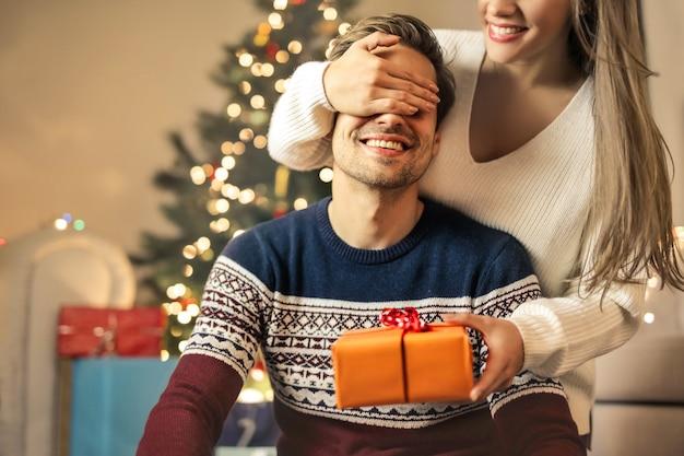 Mädchen, das ihren freund mit einem weihnachtsgeschenk überrascht Premium Fotos