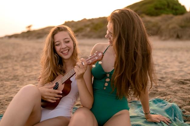 Mädchen, das ihren freund spielt ukulele am strand betrachtet Kostenlose Fotos