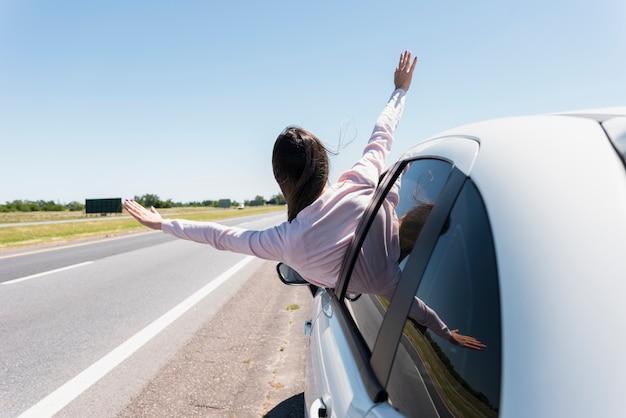 Mädchen, das ihren kopf aus dem fensterauto heraus setzt Kostenlose Fotos