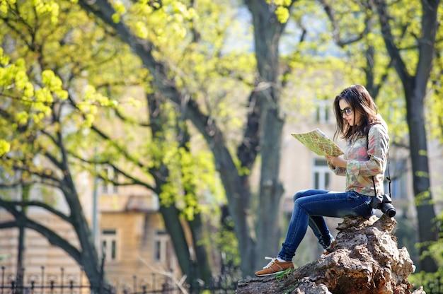 Mädchen, das im park sitzt und eine karte liest Premium Fotos