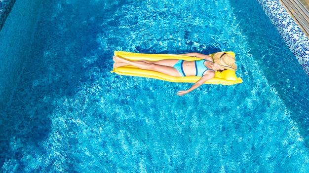Mädchen, das im schwimmbad auf aufblasbarer matratze entspannt Premium Fotos