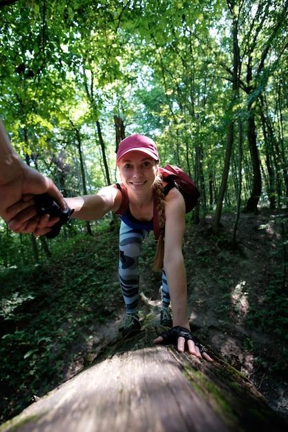 Mädchen, das im wald, kletternd bis zum klotz wandert. bemannen sie das halten der hand des mädchens versuchend zu helfen zu klettern Premium Fotos