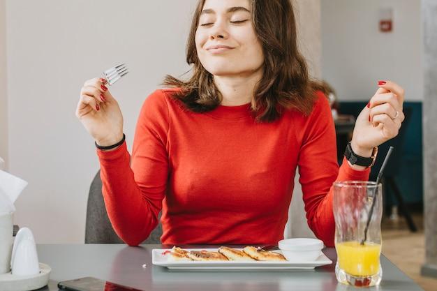 Mädchen, das in einem restaurant isst Kostenlose Fotos