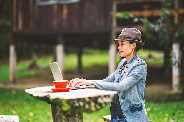 Mädchen, das kaffee auf tabelle in der ferienurlaubszeit auf hügelnatur bearbeitet und trinkt Premium Fotos