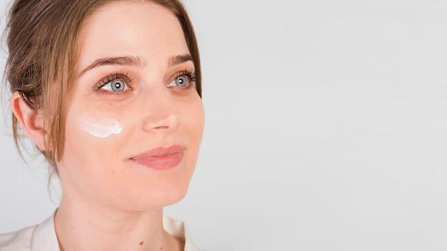 Mädchen, das kosmetisches produkt sich aufträgt Kostenlose Fotos