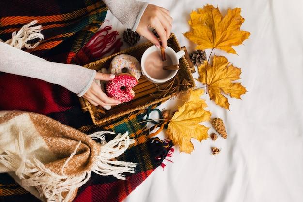 Mädchen, das leckeres frühstück im bett auf holztablett mit tasse kakao, zimt, keksen und glasierten donuts isst. Kostenlose Fotos