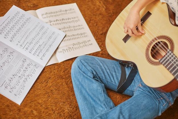 Mädchen, das lernt, wie man zu hause gitarre spielt Kostenlose Fotos
