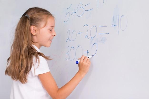 Mädchen, das mathe auf einem whiteboard tut Kostenlose Fotos