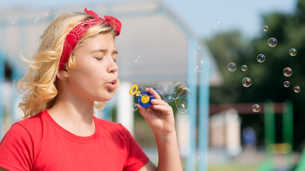 Mädchen, das mit blasengebläse im freien spielt Kostenlose Fotos