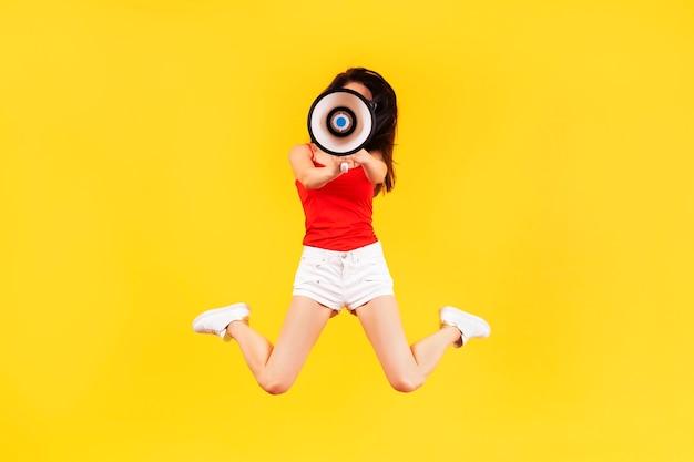 Mädchen, das mit einem megaphon auf einer gelben wand springt Premium Fotos