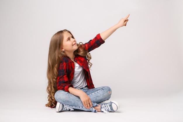 Mädchen, das mit ihrem finger auf copyspace zeigt Premium Fotos