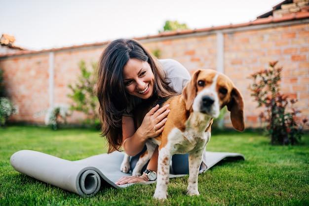 Mädchen, das mit ihrem spürhundhund im yard spielt. Premium Fotos