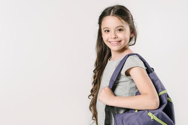 Mädchen, das mit rucksack im studio steht Premium Fotos