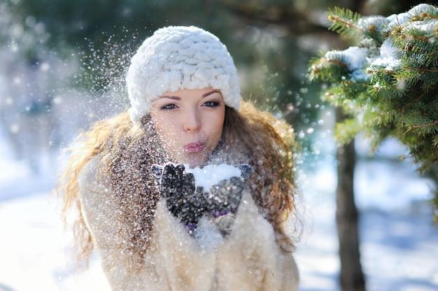 Mädchen, das mit schnee im park spielt Premium Fotos