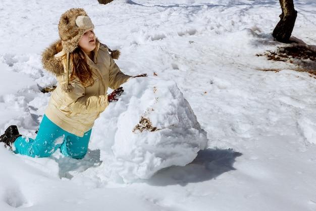 Mädchen, das mit schnee im winter am sonnigen tag spielt Premium Fotos