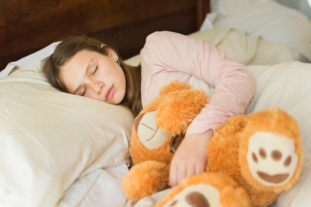 Mädchen, das mit weichem teddybären auf bett schläft Kostenlose Fotos