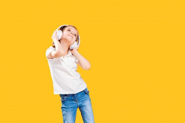 Mädchen, das musik in den drahtlosen kopfhörern hört. tanzendes mädchen. glückliches kleines mädchen, das zur musik tanzt. nettes kind, das glückliche tanzmusik genießt. Premium Fotos