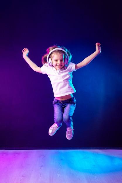 Mädchen, das musik in den kopfhörern auf dunkler bunter wand hört. tanzendes mädchen. glückliches kleines mädchen, das zur musik tanzt. nettes kind, das glückliche tanzmusik genießt. Premium Fotos