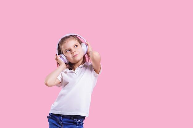Mädchen, das musik in den kopfhörern auf rosa hört. nettes kind, welches die glückliche tanzmusik, das nahe auge und die lächelnaufstellung genießt Premium Fotos