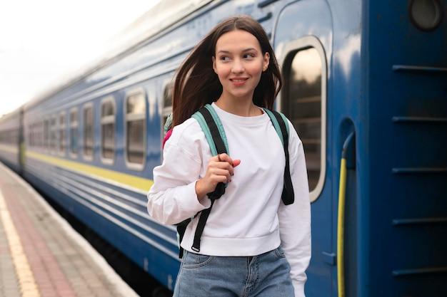 Mädchen, das neben dem zug mit ihrem rucksack steht Kostenlose Fotos
