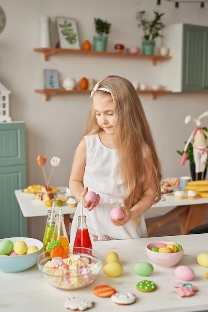Mädchen, das ostereier an der küche hält Premium Fotos