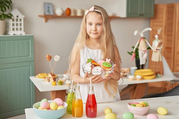 Mädchen, das osterplätzchen an der küche hält Premium Fotos