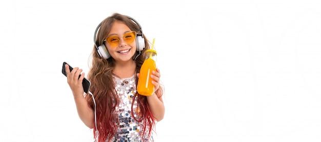 Mädchen, das prickelndes kleid und gelbe sonnenbrille, mit großen weißen kopfhörern trägt, musik hört und schwarzen smartphone und flasche mit orangensaft lokalisiert hält Premium Fotos