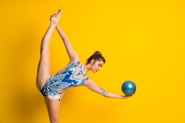 Mädchen, das rhythmische gymnastik mit ball tut Premium Fotos