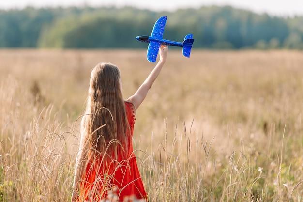 Mädchen, das schnell läuft und flugzeugspielzeug hält Premium Fotos