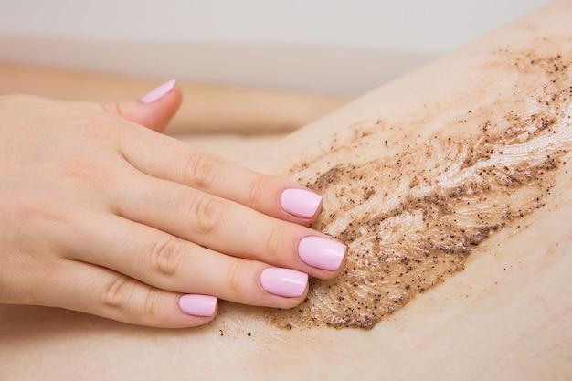 Mädchen, das schönheitsbehandlungen im badezimmer tut. kaffee-peeling für fuß Premium Fotos