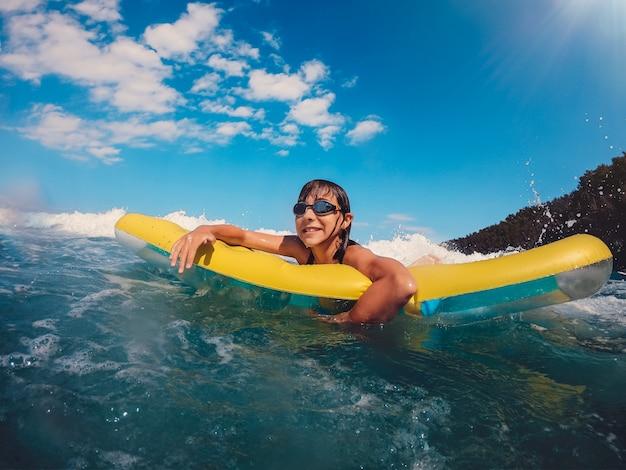 Mädchen, das spaß hat, auf die luftmatratze im meer zu schwimmen Premium Fotos