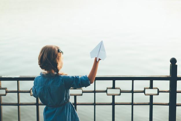 Mädchen, das spielzeugpapierflugzeug startet, das zum see schaut Kostenlose Fotos
