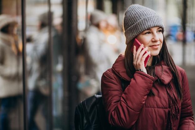 Mädchen, das telefon außerhalb der straße verwendet und freunde trifft Kostenlose Fotos