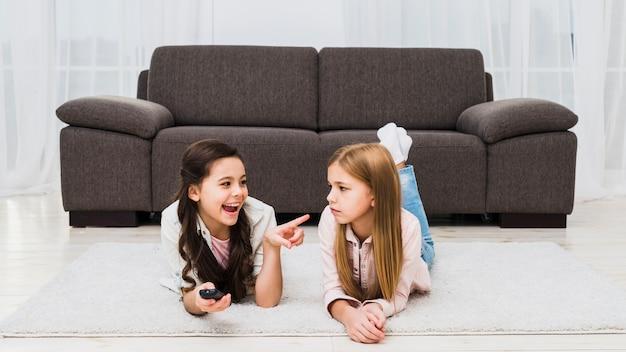 Mädchen, das unfug ihres freunds zu hause liegt auf teppich macht Kostenlose Fotos