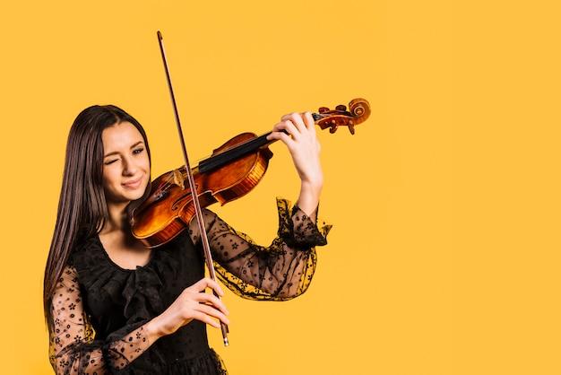 Mädchen, das violine spielend zwinkert Kostenlose Fotos