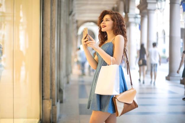 Mädchen, das vor einem schaukasten, ein foto mit ihrem smartphone machend steht Premium Fotos