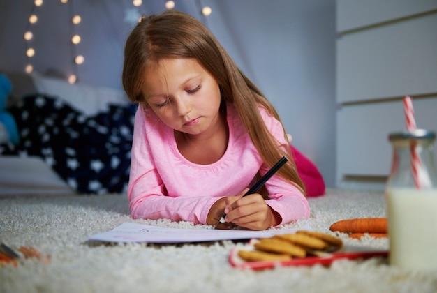 Mädchen, das vorne liegt und einen brief schreibt Kostenlose Fotos