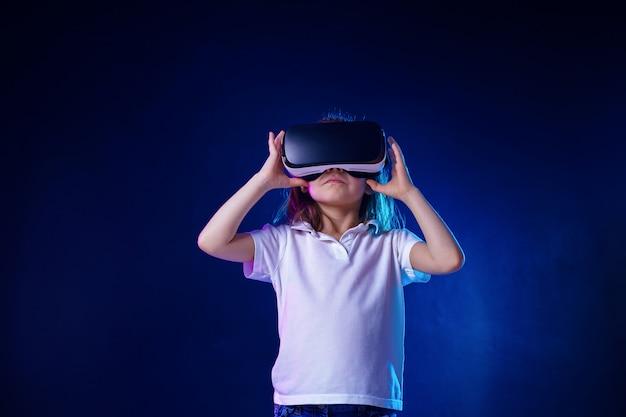 Mädchen, das vr-kopfhörerspiel erfährt. kind, das ein spielgerät für virtuelle realität verwendet. Premium Fotos