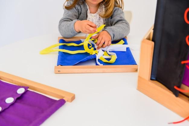 Mädchen, das wie man bindungen in einem holzrahmen übt, bindet. Premium Fotos