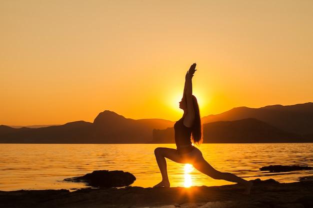 Mädchen, das yoga durch den ozean tut. Premium Fotos