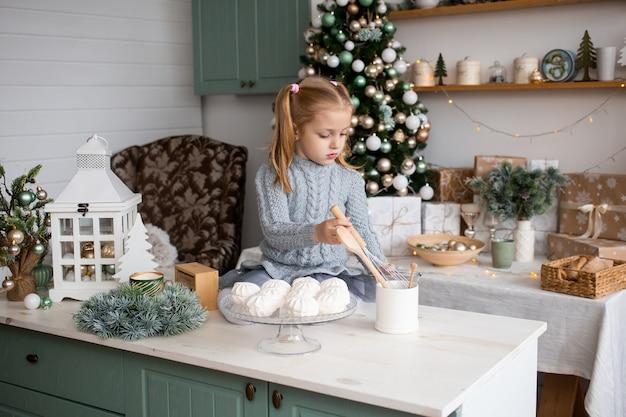 Mädchen, das zu hause in der weihnachtsmorgenküche spielt Premium Fotos